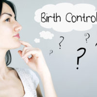 Woman next to a birth control sign.jpg.crdownload