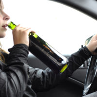 Lady drinking wine while driving