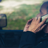 A man talking on phone while driving